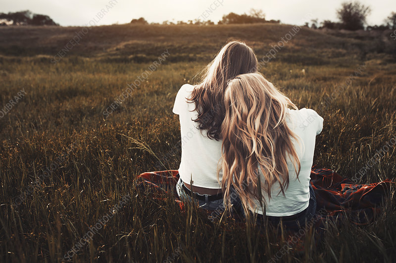 Tranquil teenage sisters in white t-shirts
