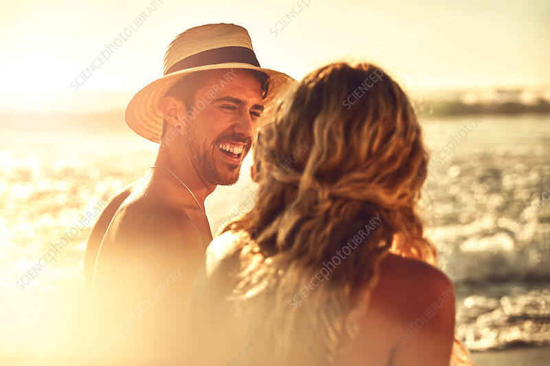 Laughing young couple on sunny summer beach