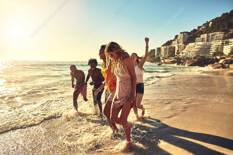 Playful young friends walking in summer ocean surf
