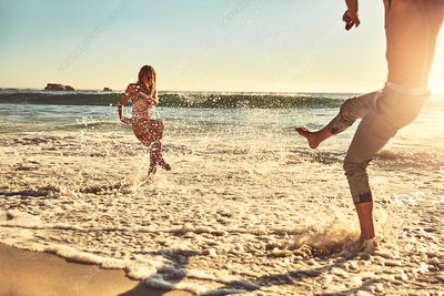 Playful young couple splashing in ocean surf