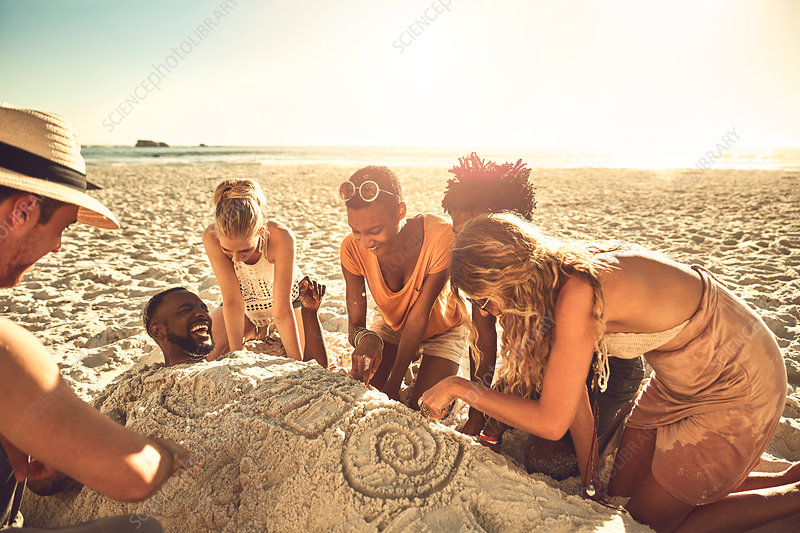 Young friends burying and drawing friend in sand