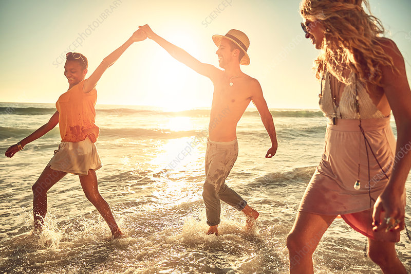 Playful young friends splashing in ocean surf