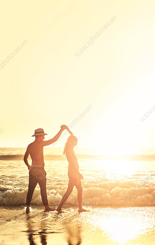 Young couple holding hands, walking on beach