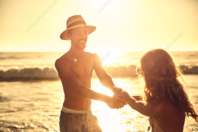 Playful young couple holding hands on beach