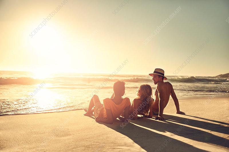 Young friends relaxing on idyllic, beach