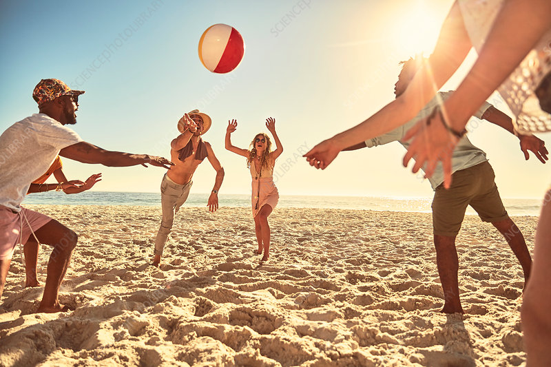 Playful young friends playing with beach ball