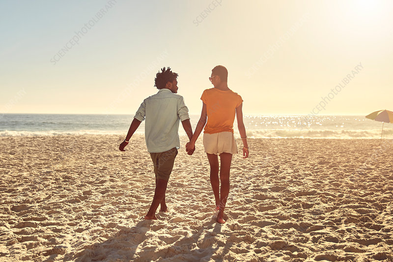 Young couple holding hands, walking