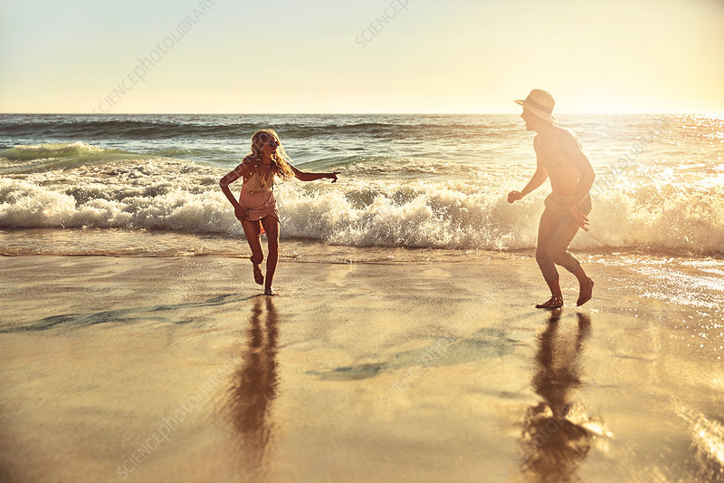 Playful young couple running in wet sand