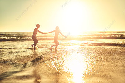 Young couple holding hands, walking in beach surf