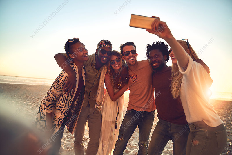 Young friends with camera phone taking selfie