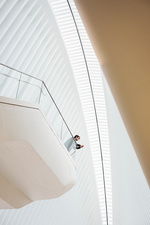 Man standing on a balcony in an atrium