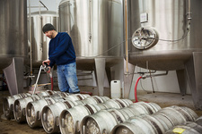 Man filling metal beer kegs in a brewery