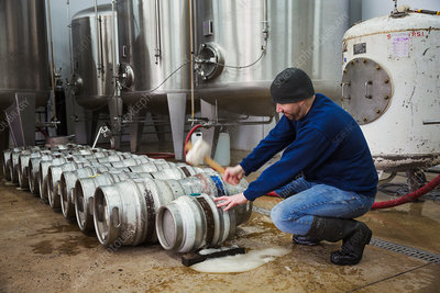 Man hammering in a peg in metal beer keg