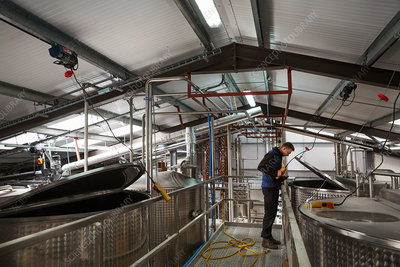 Man checking large metal tanks in brewery