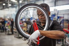 Factory worker fixing a wheel to a frame