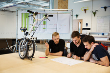 Three men meeting at a bicycle factory