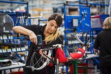 Female factory worker assembling bicycle