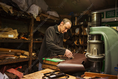 A shoemaker cutting brown leather