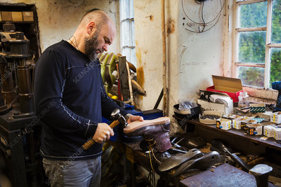 Man standing in a shoemaker's workshop