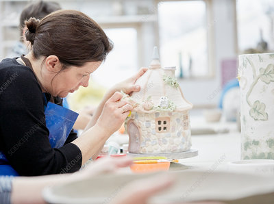 A woman working on a pottery cottage