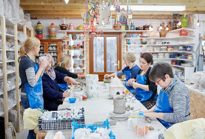 People in a pottery shop working clay