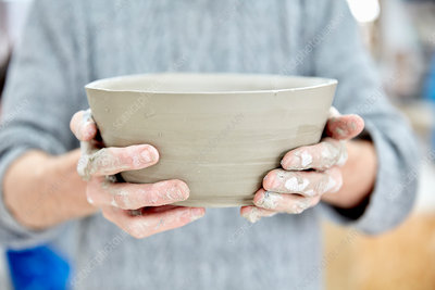 Person holding a freshly thrown clay pot
