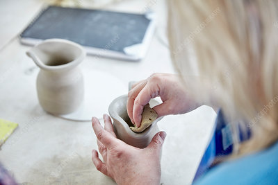 A woman using her hands on wet clay