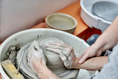 Potter seated at a wheel working clay