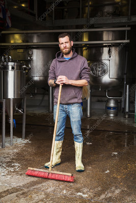 Man working in a brewery sweeping