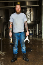Man with mallet and wrench in a brewery