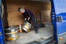 Man in a brewery loading kegs into van