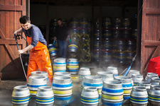 Man working, cleaning metal beer kegs