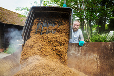 Man pouring spent grain into container