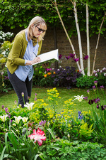 Woman in a garden drawing in a notebook