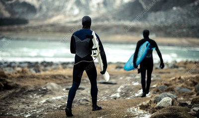 Two surfers with wetsuits and surfboards