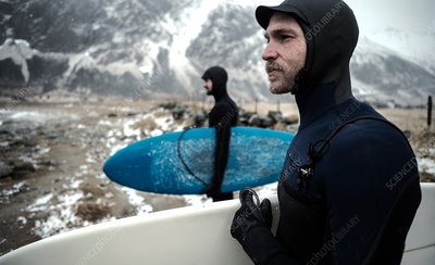 Two surfers wearing wetsuits