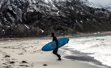 An Arctic surfer in a wetsuit