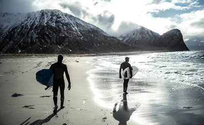 Two surfers carrying surfboards in winter