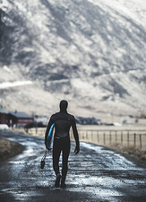 Surfer walking on a road with a surfboard