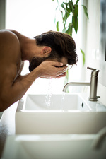 A man at a sink washing his face