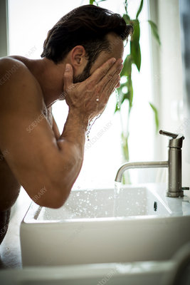 A man in a bathroom washing his face