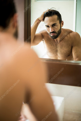 A man by a bathroom mirror