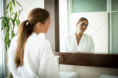 A woman standing in front of mirror