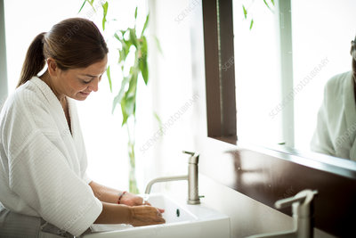 A woman at a bathroom sink with mirror