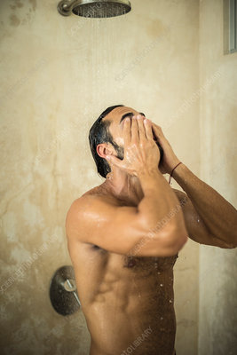 A man standing in a shower in a bathroom