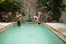 Two children doing backflips into pool
