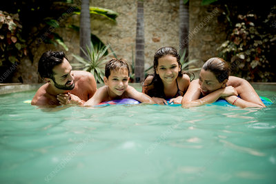 A family resting on a pool raft in a pool