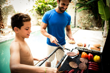 A man and boy at a barbecue cooking food