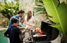 A family cooking food on a barbeque