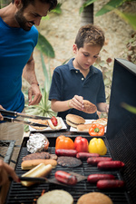 A man and boy at barbecue cooking food